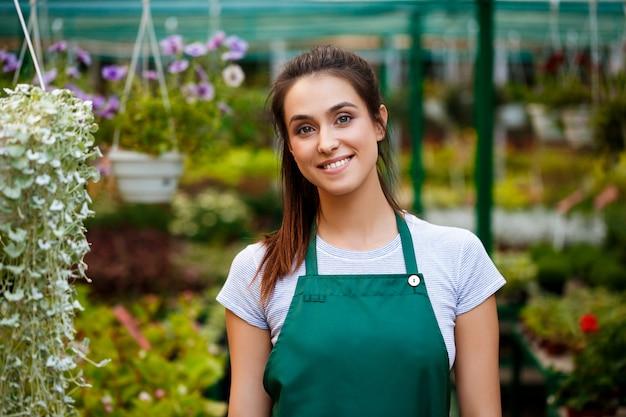 Floristería hermosa joven posando, sonriendo entre flores.