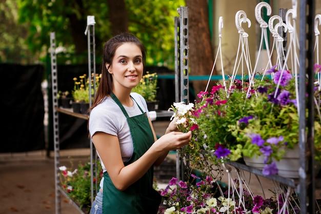 Floristería hermosa joven que cuida las flores.