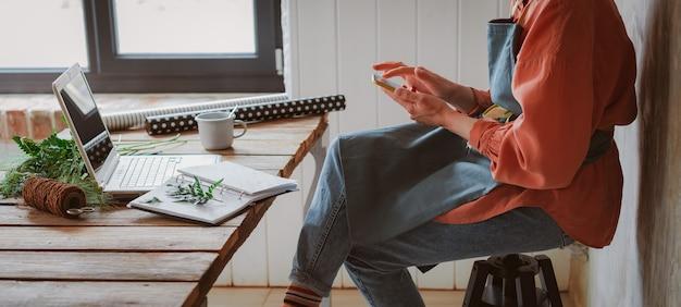 Floristería de hipster chica con estilo de moda en un delantal de trabajo trabajando en una computadora portátil mirando un teléfono inteligente comprobar las tiendas en línea para las ventas de tecnología cyber monday