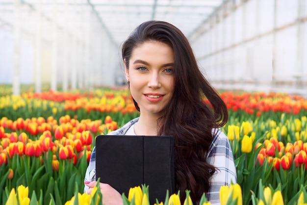 Floristería mujer sonriente joven está de pie con una tableta en sus manos en un invernadero