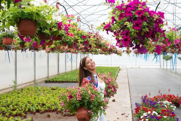 Floristería sonriente feliz arreglando flores y disfrutando del trabajo en el jardín de invernadero