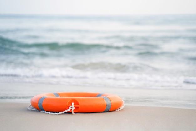 Flotador de anillo de piscina salvavidas rojo. anillo de vida en la arena del mar.