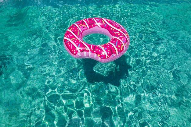 Flotador inflable de donas rociadas modernas en la pared de la piscina soleada directamente sobre el agua clara y brillante de la piscina concepto de verano, relax y estilo de vida