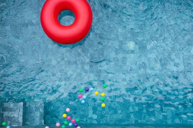 Flotador rojo de la piscina, anillo que flota en una refrescante piscina azul con sombra de árbol de coco.