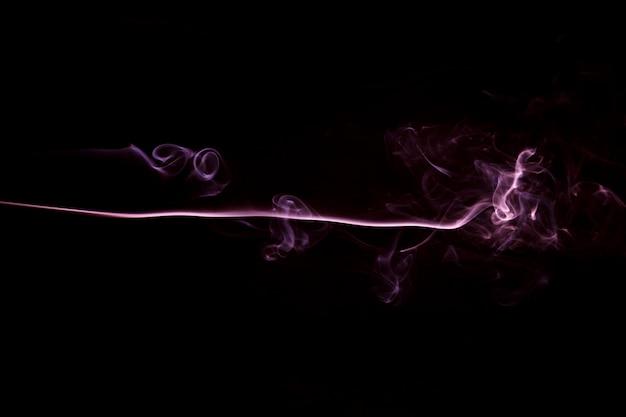 Flujo de humo rosa sobre fondo negro con espacio de copia