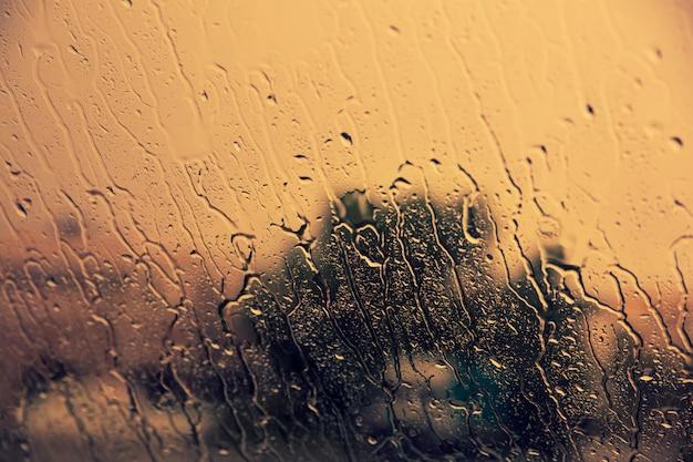 Fluyendo hacia abajo las gotas de lluvia en el parabrisas del coche. concepto de otoño