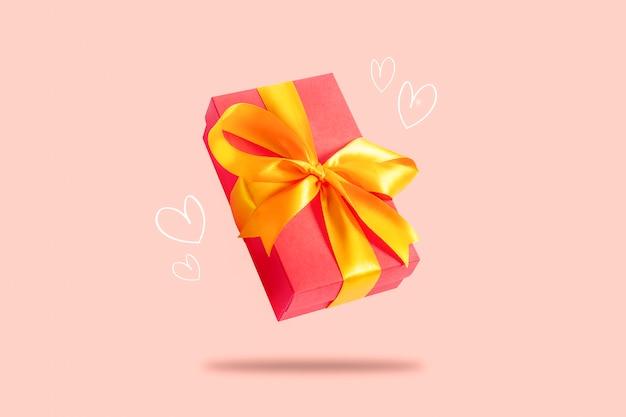 Flying caja de regalo sobre una superficie de color rosa claro con corazones. concepto de vacaciones, regalo, venta, boda y cumpleaños.