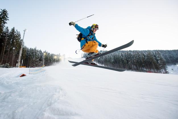 Flying esquiador hombre en salto desde la ladera de las montañas realizando un salto de altura y mirando aprensivo sobre el aterrizaje con bosque en segundo plano.