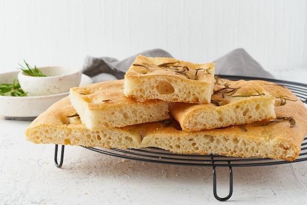 Focaccia, pizza, pan plano italiano con romero y aceite de oliva en rejilla
