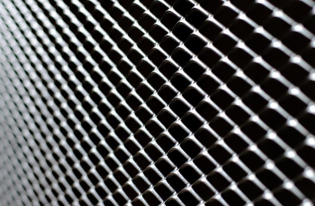 Foco y borroso de gris oscuro y rejilla plateada de cerca metálica.