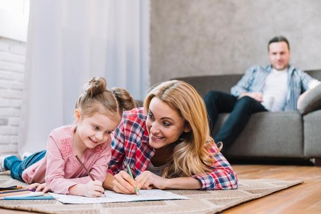 Foco borroso del padre que mira a su esposa e hija mientras que dibuja en el libro