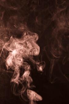 Foco de la luz en el arte de humo blanco sobre fondo negro