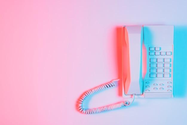 Foco de luz azul en el teléfono fijo rosa sobre el fondo rosa