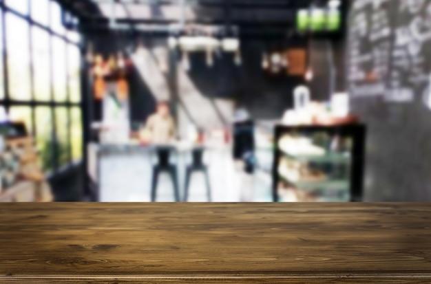 El foco seleccionado vacia la tabla de madera marrón y la cafetería o el restaurante desdibujan el fondo