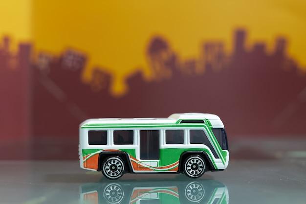 Foco selectivo del juguete del autobús que viaja de la lanzadera en ciudad de la falta de definición