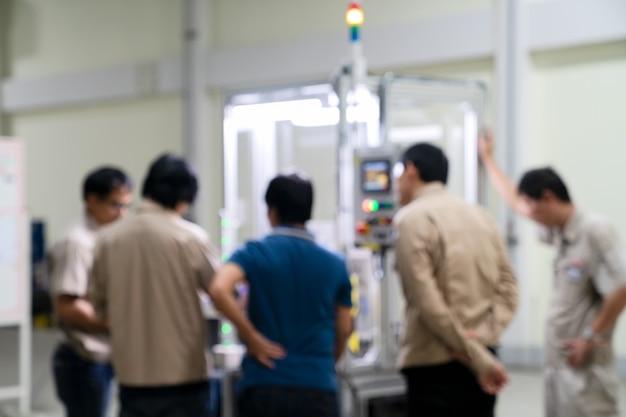 Focos de desenfoque del ingeniero de fábrica comprueba la calidad de la pieza fabricada