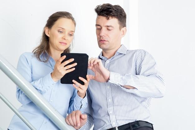 Focused hombre de negocios y la mujer usando tableta