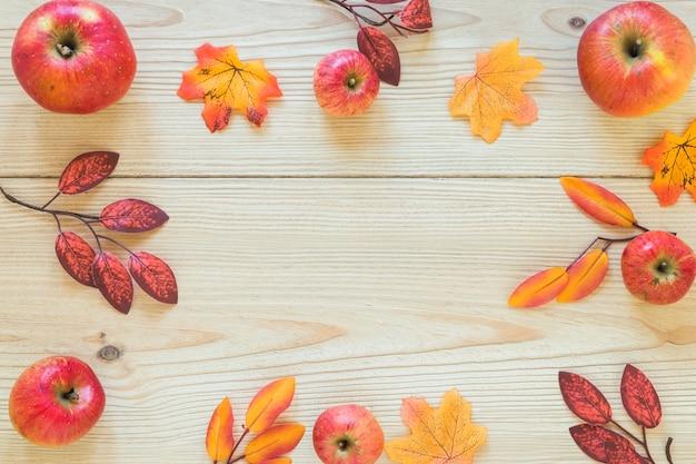 Follaje y frutas sobre tablero de madera.