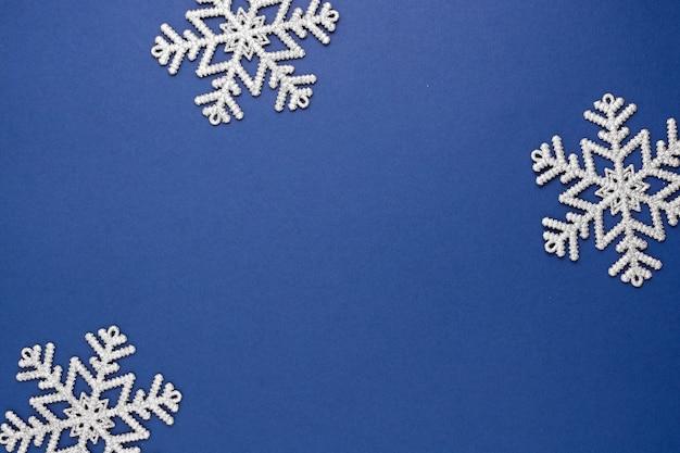 Fondo abstracto azul de navidad con copos de nieve de plata decoración de invierno, azul simulacro con espacio para texto.