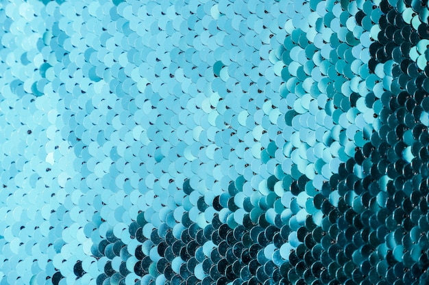 Fondo abstracto con color azul de lentejuelas en la tela. escamas de textura de lentejuelas redondas con transición de color.