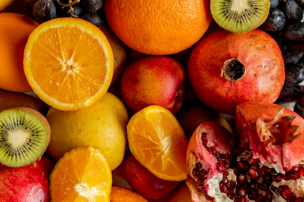 Fondo abstracto con frutas orgánicas frescas como las uvas de kiwi naranja en rodajas y granates