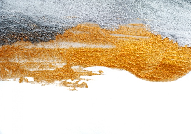 Fondo abstracto pintado con un pincel de pintura dorada y plateada