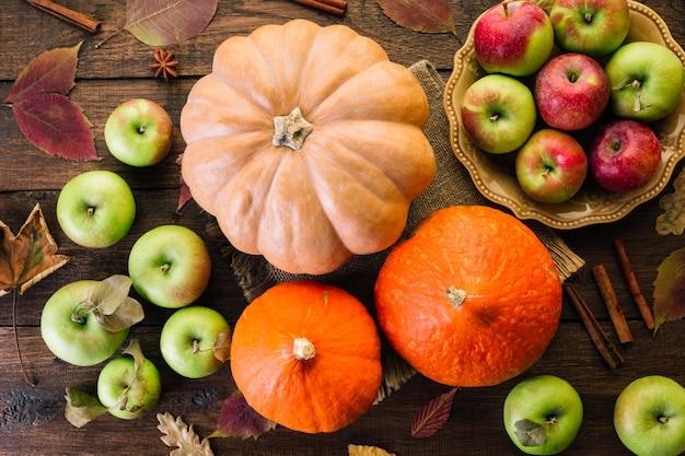 Fondo de acción de gracias, calabazas, manzanas y especias en una mesa de madera