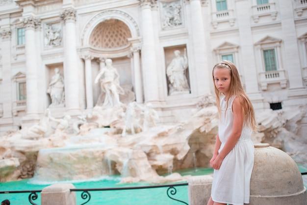 Fondo adorable de la niña fuente de trevi, roma, italia.