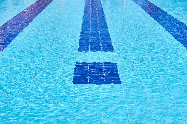 Fondo de agua en la piscina azul, superficie del agua con un reflejo del sol