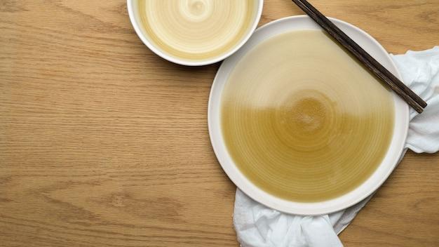 Fondo de ajuste de tabla, simulacros de platos de cerámica, mantel y palillos en la mesa de madera, vista superior, espacio de copia