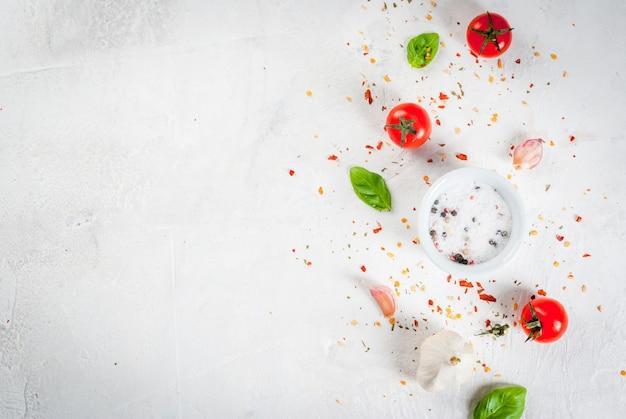 Fondo de alimentos ingredientes, verduras y especias para cocinar el almuerzo. hojas frescas de albahaca, tomates, ajo, cebolla, sal, pimienta. sobre una mesa de piedra blanca. copia espacio vista superior