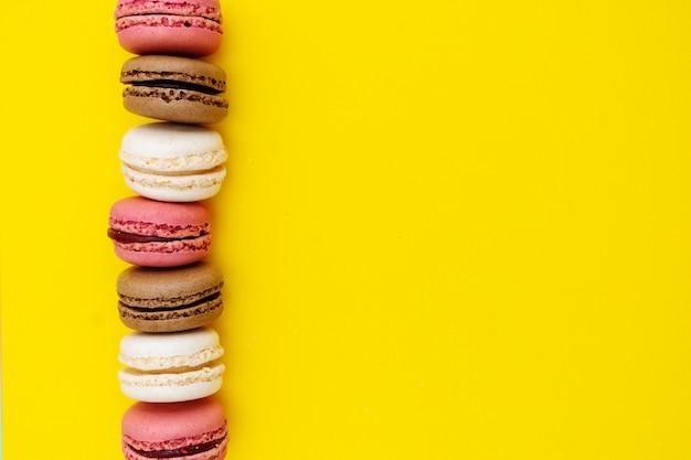 Fondo de alimentos con pasteles de macarrones sobre fondo amarillo.
