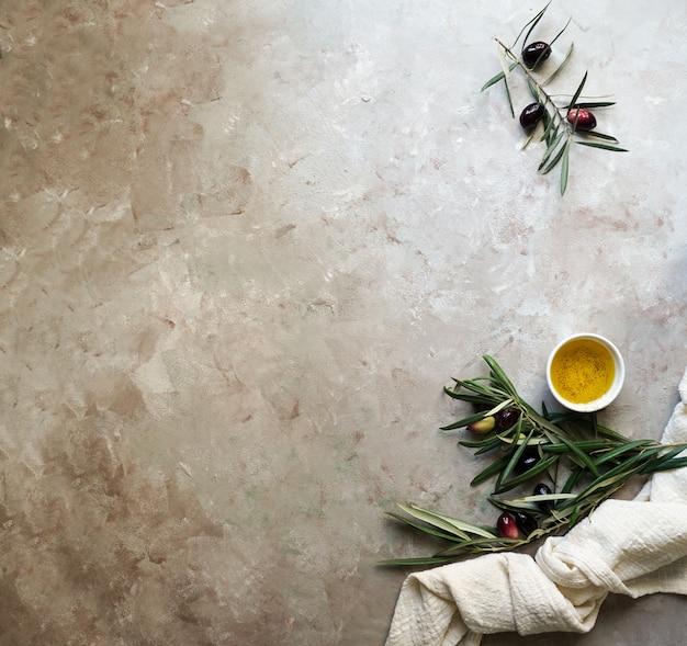 Fondo de alimentos con rama de olivo, servilleta y plato, cuchillo y tenedor cubiertos, aceite de oliva sobre fondo de hormigón