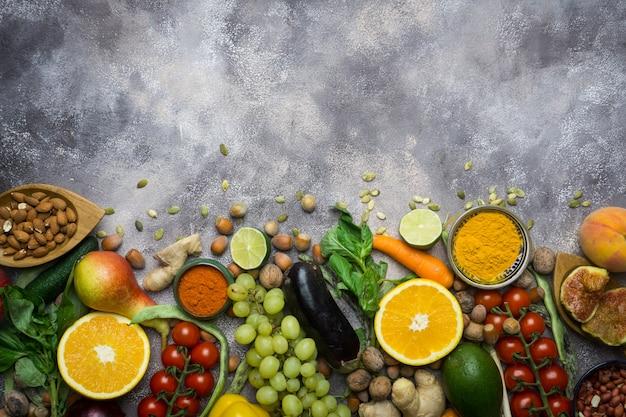 Fondo de alimentos saludables, marco de alimentos orgánicos. ingredientes para una cocina saludable: verduras, frutas, nueces, especias.