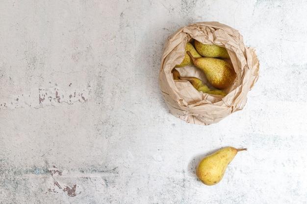 Fondo de alimentos saludables con peras maduras en una bolsa de papel beige.