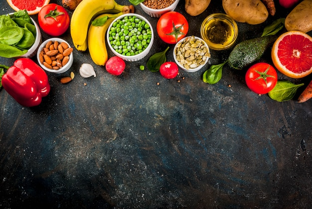 Fondo de alimentos saludables, productos de dieta alcalina de moda: frutas, verduras, cereales, nueces. aceites, vista superior de fondo de hormigón azul oscuro