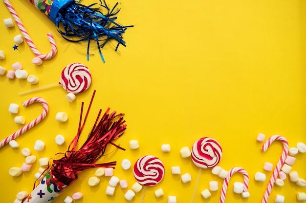 Fondo amarillo con dulces de cumpleaños