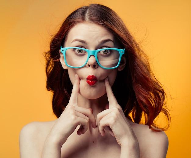 Fondo amarillo de lujo de los vidrios de los labios rojos de los hombros desnudos de la mujer bonita. foto de alta calidad