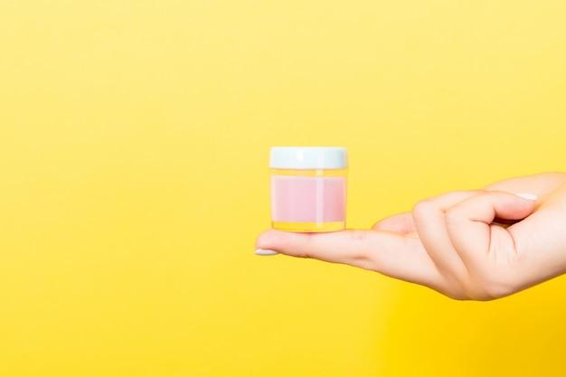 Fondo amarillo con mano femenina sosteniendo tarro de cosméticos y copia espacio para su diseño