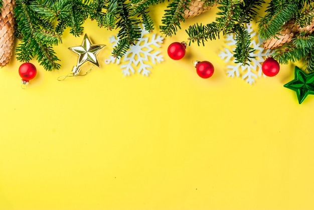 Fondo amarillo de navidad con ramas de abeto, piñas y bolas de árbol de navidad espacio de copia sobre el marco