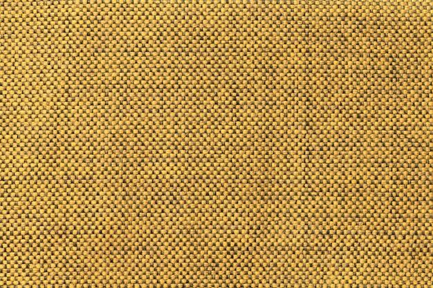 Fondo amarillo oscuro textil con patrón de ajedrez, primer plano. estructura de la macro de la tela.