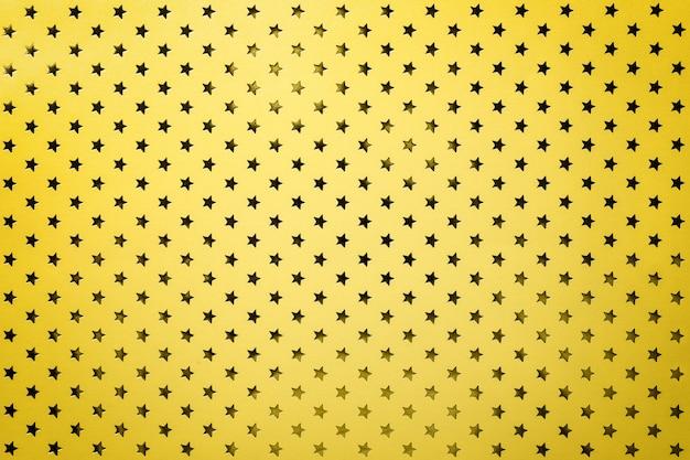 Fondo amarillo de papel de aluminio con un patrón de estrellas doradas