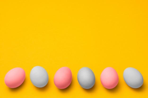 Fondo amarillo de pascua con espacio de copia. huevos rosados y blancos en una fila en la parte inferior