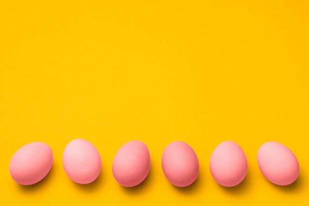 Fondo amarillo de pascua con una fila de huevos de color rosa con espacio de copia en la parte superior