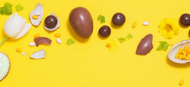 Fondo amarillo de pascua con huevos de chocolate, dulces y spri