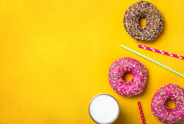 Fondo amarillo postre con varios donuts y leche