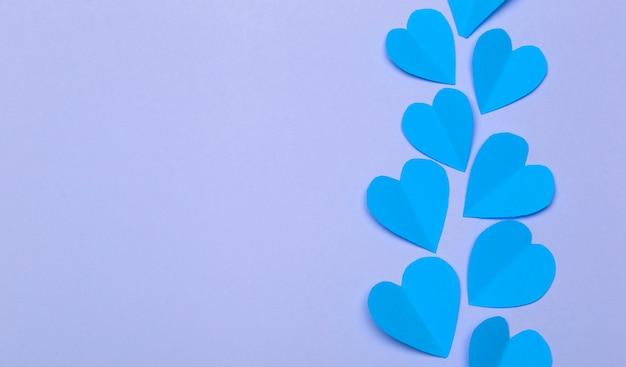 Fondo de amor (día de san valentín) o fondo de boda. corazones de papel azul sobre un fondo morado pastel. concepto de amor