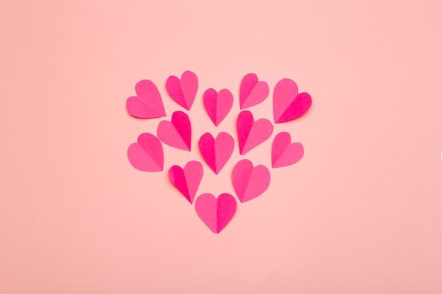 Fondo de amor (día de san valentín) o fondo de boda. corazones de papel rosa sobre un fondo rosa pastel. concepto de amor