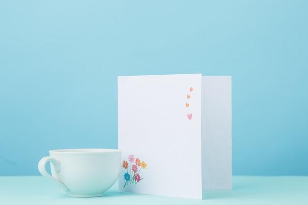 Fondo de amor con tarjeta y taza de regalo en la mesa