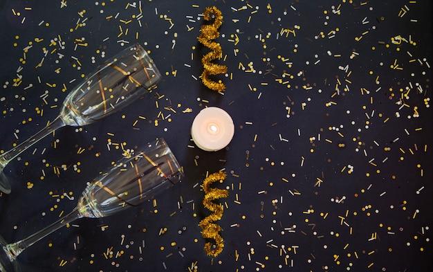 Fondo de año nuevo con copas de champán y confeti